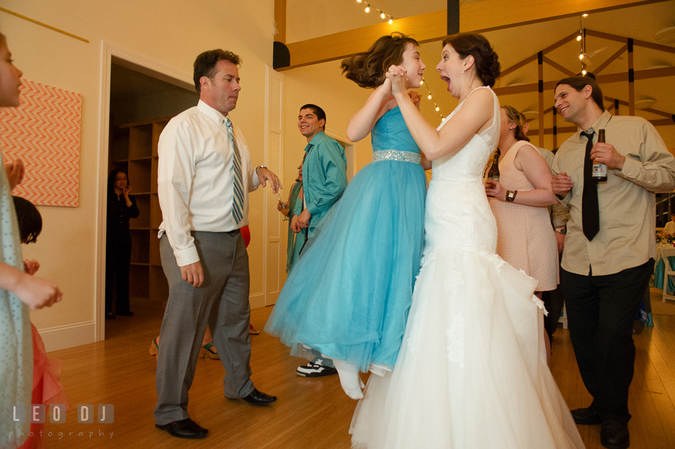 Flower girl jumping high while dancing with Bride. Chesapeake Bay Environmental Center, Eastern Shore Maryland, wedding reception and ceremony photo, by wedding photographers of Leo Dj Photography. http://leodjphoto.com