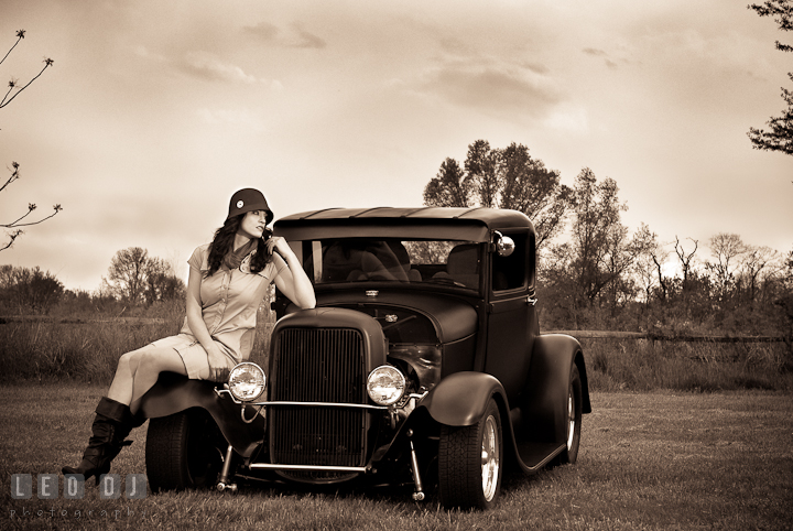Black and white photo of girl with vintage Hollywood style pose and lighting on an antique Ford model car. Model portrait session with Brittany from Beyond the Veil music Band and her Siberian Husky pet dog at Kent Island, Maryland Eastern Shore by photographer Leo Dj Photography.