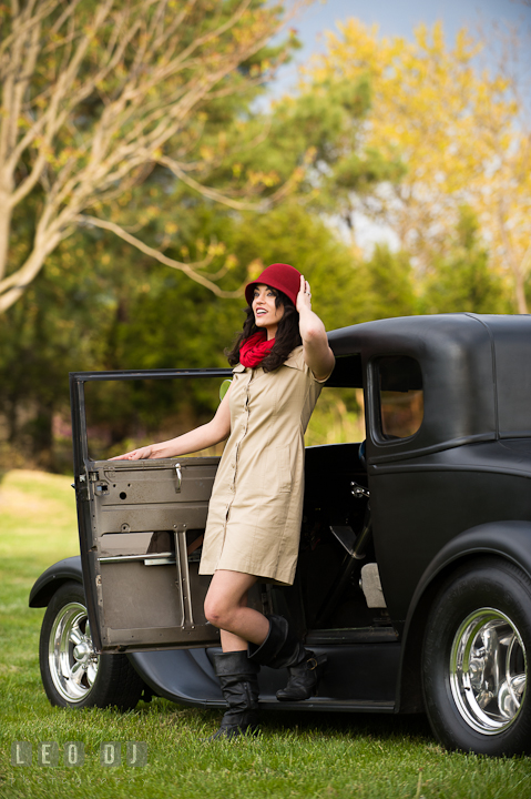 Girl stepping out of a vintage Ford model car, holding her red hat. Model portrait session with Brittany from Beyond the Veil music Band and her Siberian Husky pet dog at Kent Island, Maryland Eastern Shore by photographer Leo Dj Photography.