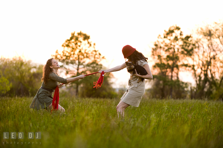 Girl with red hat playing tug o' war with her sister. Model portrait session with Brittany from Beyond the Veil music Band and her Siberian Husky pet dog at Kent Island, Maryland Eastern Shore by photographer Leo Dj Photography.