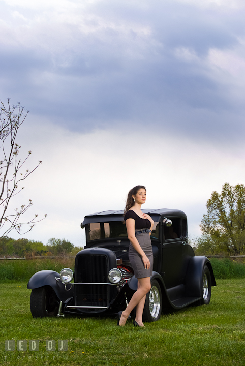 Girl posing by an antique Ford car. Dark clouds behind them. Eastern Shore, Maryland, Kent Island High School senior portrait session by photographer Leo Dj Photography. http://leodjphoto.com