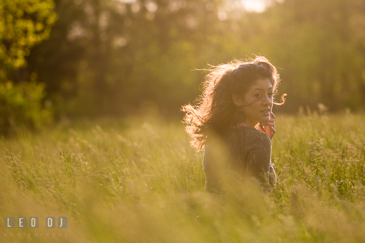 Girl in grass meadow looking back while wind blowing her hair. Eastern Shore, Maryland, Kent Island High School senior portrait session by photographer Leo Dj Photography. http://leodjphoto.com