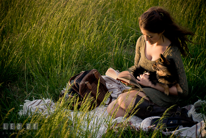 Girl in a grass meadow reading her book accompanied by her pet dog. Eastern Shore, Maryland, Kent Island High School senior portrait session by photographer Leo Dj Photography. http://leodjphoto.com