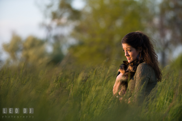 Girl in a grass field holding her pet dog looking at the sunset. Eastern Shore, Maryland, Kent Island High School senior portrait session by photographer Leo Dj Photography. http://leodjphoto.com