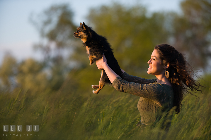 Girl in a grass meadow holding up her pet dog high up in the air. Eastern Shore, Maryland, Kent Island High School senior portrait session by photographer Leo Dj Photography. http://leodjphoto.com