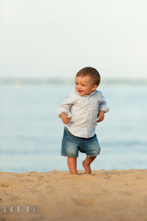 Little toddler boy walking on the beach and smiling. Kent Island, Annapolis, Eastern Shore Maryland candid children and family lifestyle portrait photo session by photographers of Leo Dj Photography. http://leodjphoto.com