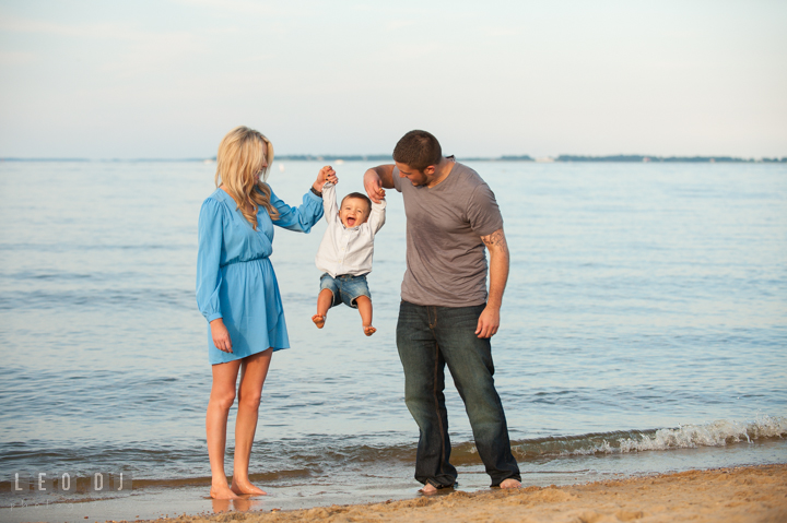 Mom and Dad on the beach playing together with their Son lifting him up. Kent Island, Annapolis, Eastern Shore Maryland candid children and family lifestyle portrait photo session by photographers of Leo Dj Photography. http://leodjphoto.com