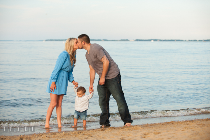 Mom and Dad kissing while holding their child in the middle. Kent Island, Annapolis, Eastern Shore Maryland candid children and family lifestyle portrait photo session by photographers of Leo Dj Photography. http://leodjphoto.com