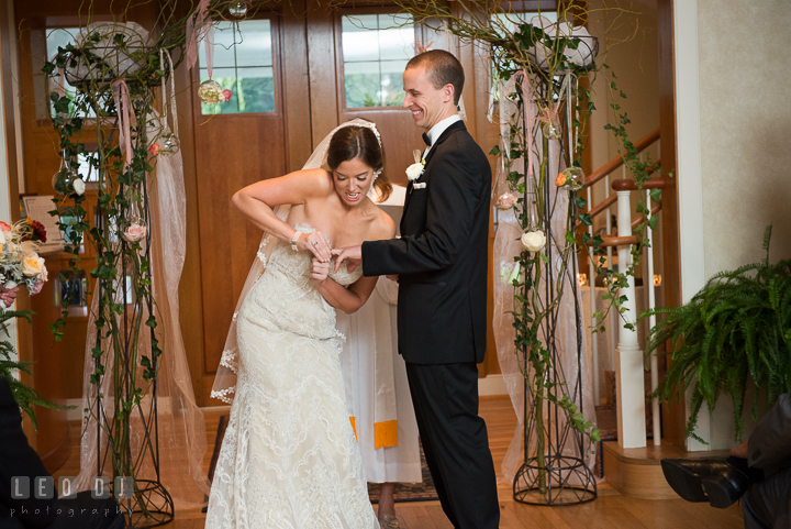 Bride strugling hard to put Groom's wedding band during ceremony. Aspen Wye River Conference Centers wedding at Queenstown Maryland, by wedding photographers of Leo Dj Photography. http://leodjphoto.com