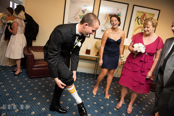 Groom showing soccer sport socks to his family. Aspen Wye River Conference Centers wedding at Queenstown Maryland, by wedding photographers of Leo Dj Photography. http://leodjphoto.com