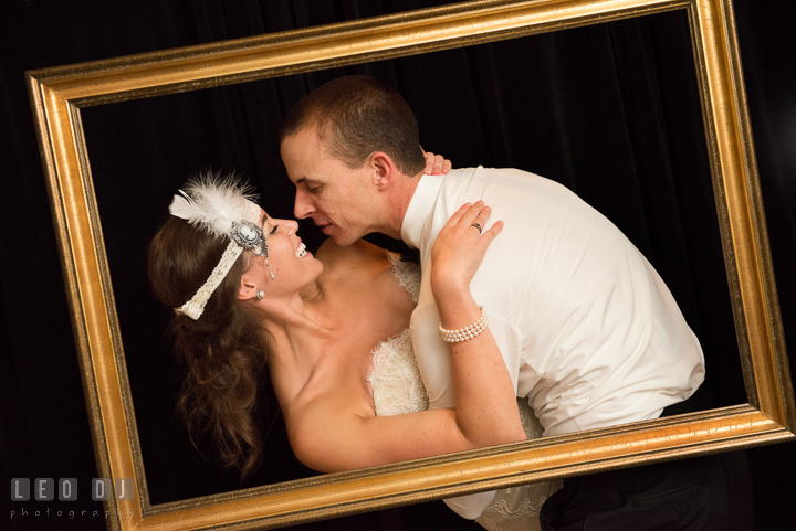Bride and Groom with art deco style headband posing inside a golden wooden frame doing the dip. Aspen Wye River Conference Centers wedding at Queenstown Maryland, by wedding photographers of Leo Dj Photography. http://leodjphoto.com
