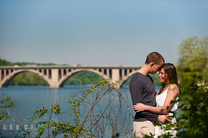 Engaged couple hugging by DC Waterfront with the Francis Scott Key Bridge in the background. Georgetown Washington DC pre-wedding engagement photo session, by wedding photographers of Leo Dj Photography. http://leodjphoto.com