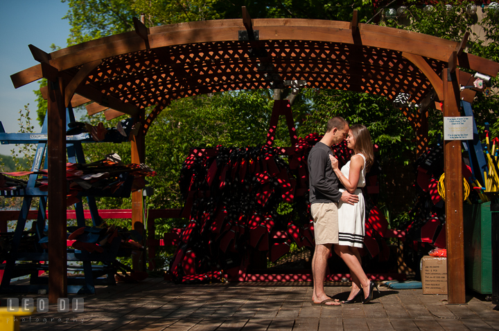 Engaged guy hugging his fiancée under a canopy. Georgetown Washington DC pre-wedding engagement photo session, by wedding photographers of Leo Dj Photography. http://leodjphoto.com