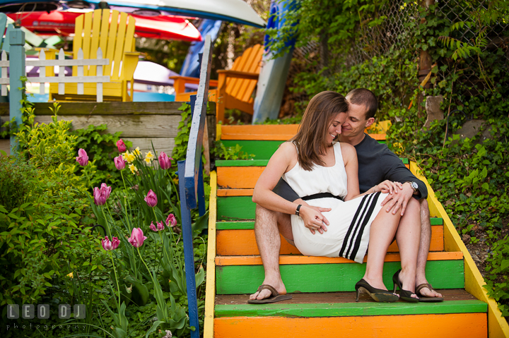 Engaged couple cuddling on colorful stairs, with tulips on the side. Georgetown Washington DC pre-wedding engagement photo session, by wedding photographers of Leo Dj Photography. http://leodjphoto.com