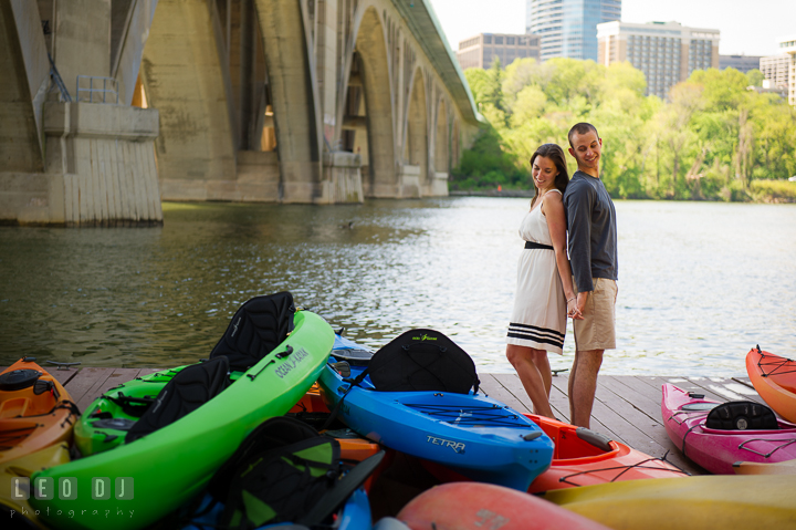 Engaged couple having their backs against each other's holding hands, surrounded by canoes by the Key Bridge. Georgetown Washington DC pre-wedding engagement photo session, by wedding photographers of Leo Dj Photography. http://leodjphoto.com