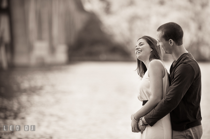 Engaged couple cuddling and laughing together by the Potomac Riverfiancée. Georgetown Washington DC pre-wedding engagement photo session, by wedding photographers of Leo Dj Photography. http://leodjphoto.com