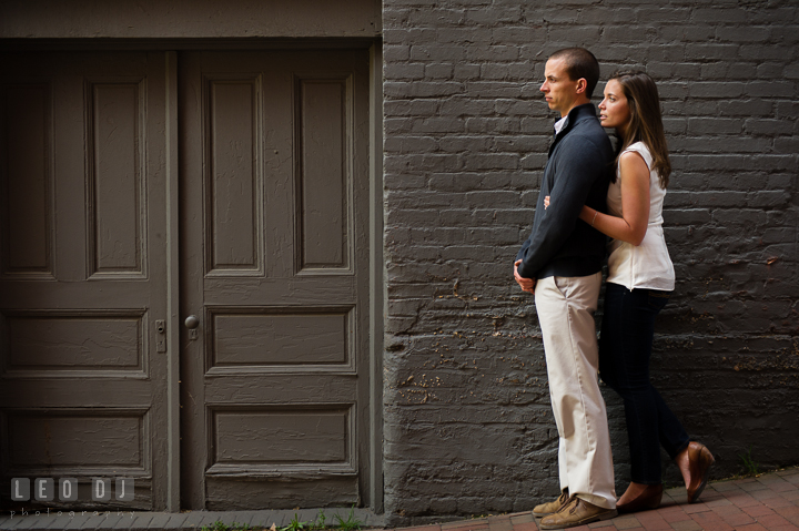 Engaged guy hugged by his fiancée by green doors in an alley. Georgetown Washington DC pre-wedding engagement photo session, by wedding photographers of Leo Dj Photography. http://leodjphoto.com