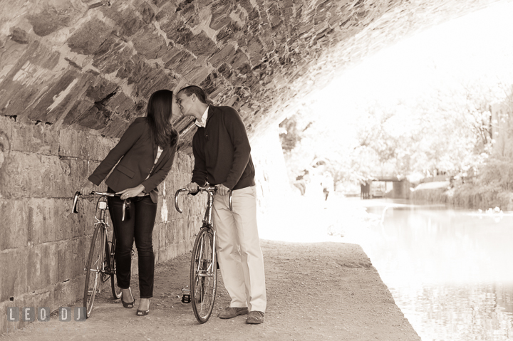 Engaged couple holding bicycles and kissed under a stone bridge over the C&O canal. Georgetown Washington DC pre-wedding engagement photo session, by wedding photographers of Leo Dj Photography. http://leodjphoto.com