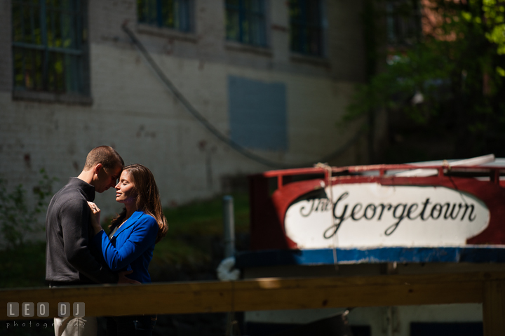 Engaged guy hugging with his fiancée at the C&O Canal with The Georgetown boat in the background. Georgetown Washington DC pre-wedding engagement photo session, by wedding photographers of Leo Dj Photography. http://leodjphoto.com