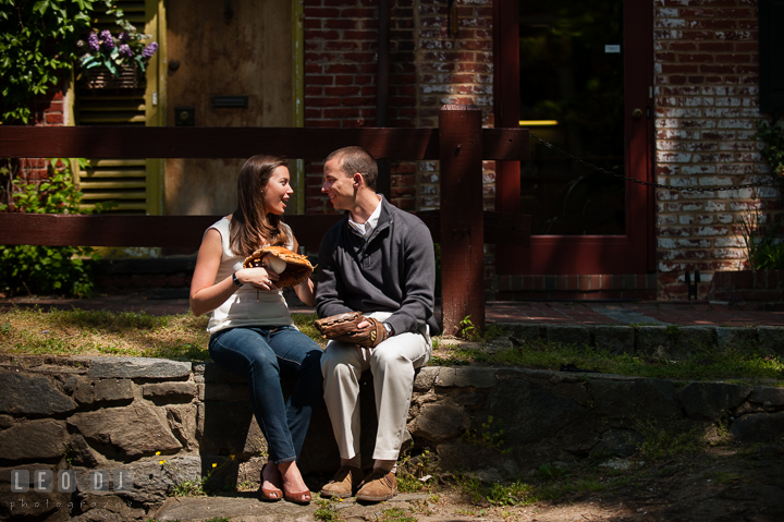 Engaged couple sitting by the homes at C&O Canal holding baseball gloves. Georgetown Washington DC pre-wedding engagement photo session, by wedding photographers of Leo Dj Photography. http://leodjphoto.com