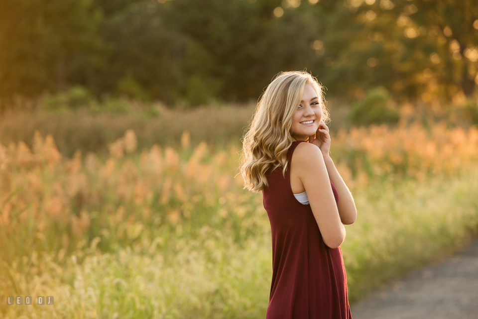 Kent Island High School Maryland senior in grass field smiling photo by Leo Dj Photography