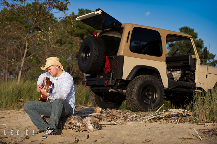 Guy with straw hat sitting on the beach and playing guitar by his SUV. Eastern Shore, Maryland, Kent Island High School senior portrait session by photographer Leo Dj Photography. http://leodjphoto.com