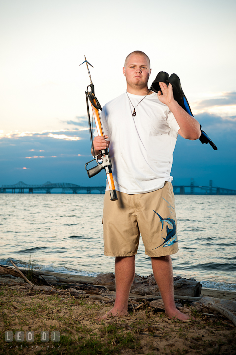 Guy holding flippers and speargun with the Chesapeake Bay Bridge in the background. Eastern Shore, Maryland, Kent Island High School senior portrait session by photographer Leo Dj Photography. http://leodjphoto.com