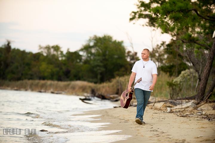 Guy carrying guitar walking on the beach. Eastern Shore, Maryland, Kent Island High School senior portrait session by photographer Leo Dj Photography. http://leodjphoto.com
