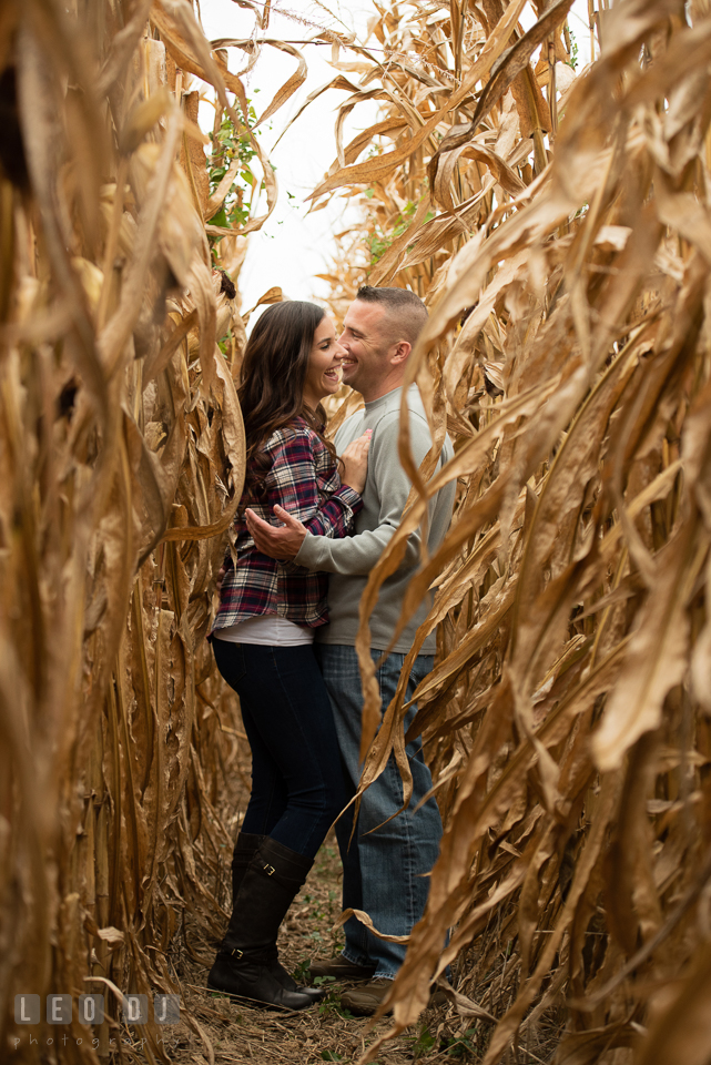 Wye Island Queenstown Maryland couple hugging and laughing in between corn stalk engagement photo by Leo Dj Photography.